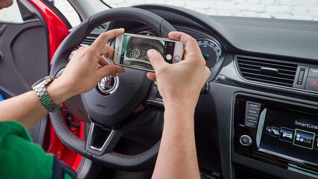 Мужчина делает фото в салоне машины на смартфон