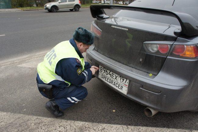 Инспектор ГИБДД снимает номер с машины