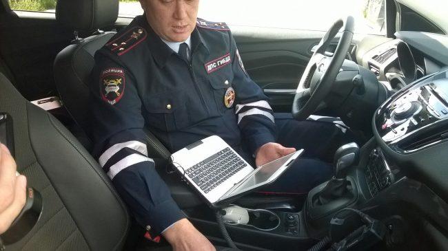 Инспектор ГИБДД с ноутбуком в автомобиле