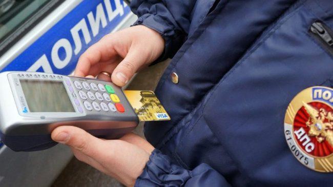 Инспектор ГИБДД списывает с карты штраф