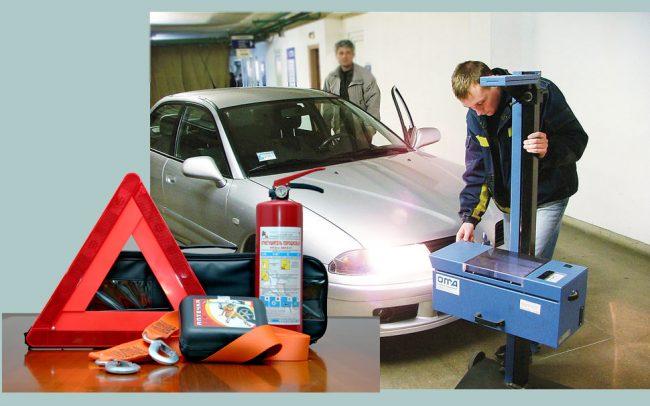 Огнетушитель, аптечка и знак аварийной остановки на фоне машины при осмотре