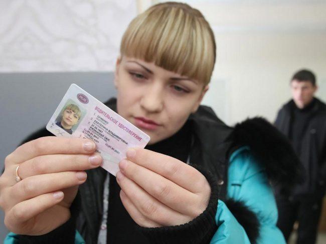 Девушка рассматривает водительское удостоверение