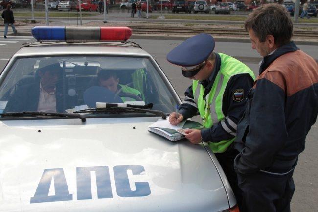 Инспектор ГИБДД штрафует водителя за нарушение ПДД
