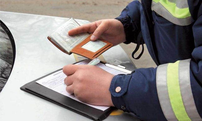 Инспектор выписывает штраф за нарушение правил дорожного движения