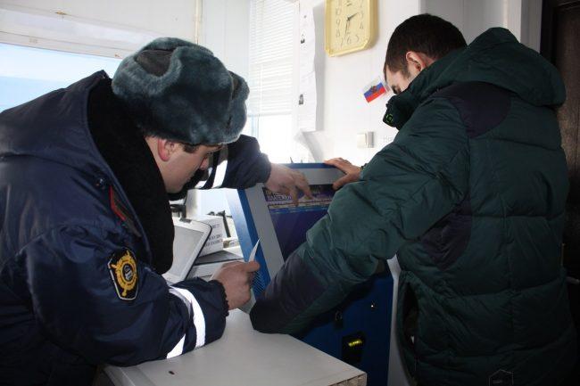 Инспектор ГИБДД помогает водителю проверить наличие штрафов в терминале