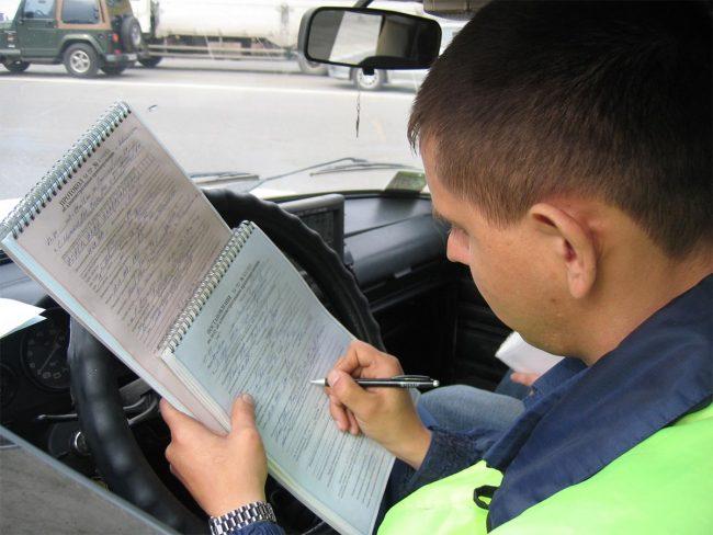 Инспектор ГИБДД выписывает штраф правонарушителю