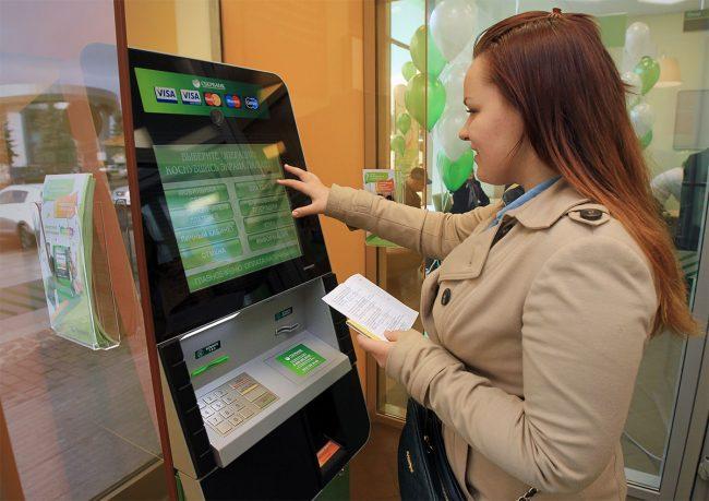 Девушка с квитанцией у терминала Сбербанка