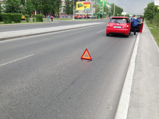 Автомобиль на дороге и знак вынужденной остановки