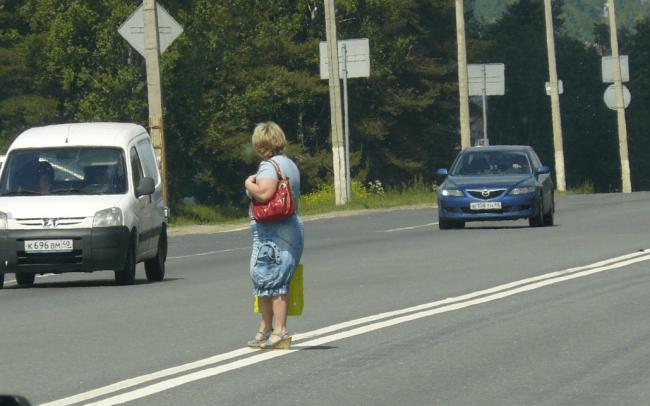Женщина стоит на разделительной полосе