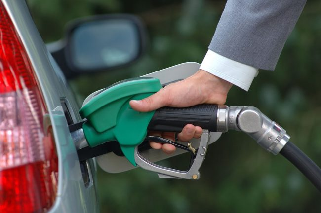 Мужчина заправляет машину бензином